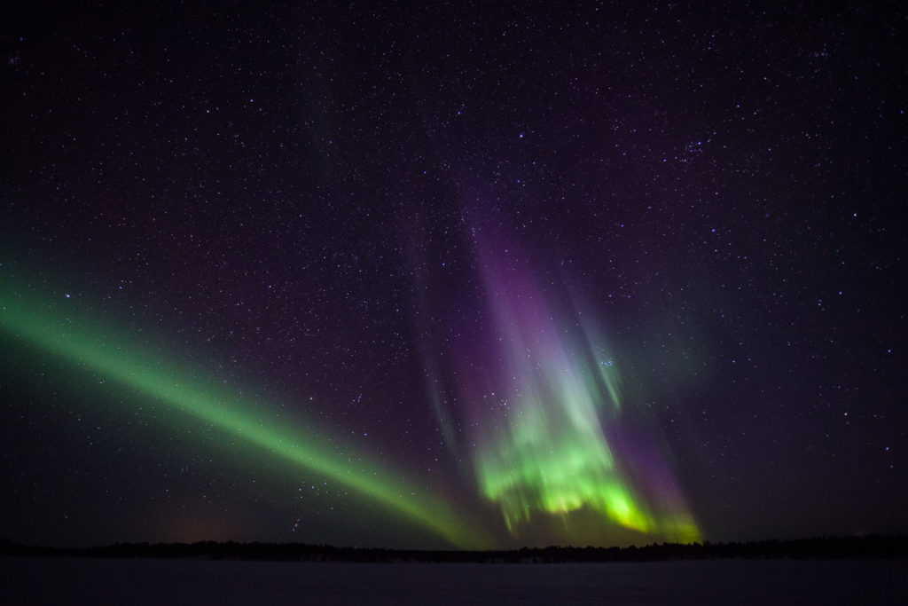 photo d'aurores boréales violettes et vertes sur un lac gelé en suède, près de al frontière avec la Norvège.